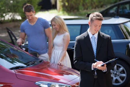 Young salesman writing on clipboard with couple looking at new car  Stock Photo