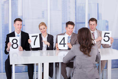 Business people showing score cards in front of female candidate during interview photo