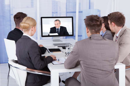 monitor: Group of business people in video conference at meeting table Stock Photo