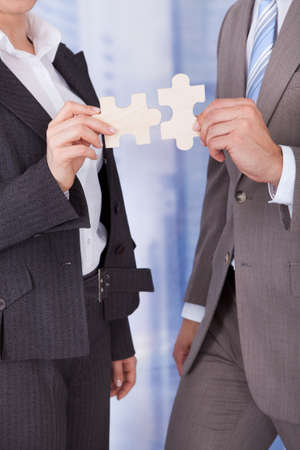 Midsection of businessman and businesswoman joining jigsaw pieces in office photo