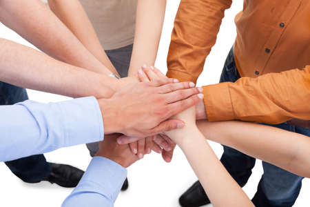 high spirits: Closeup of young friends with their hands stacked together over white  Stock Photo