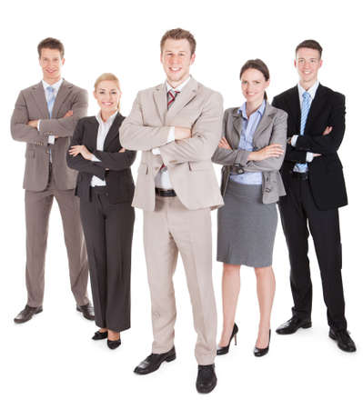 Full length portrait of confident business team standing arms crossed against white background photo