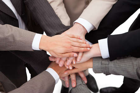 high spirits: High angle view of business people stacking hands against white background