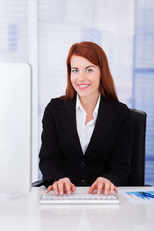 beautiful redhead: Happy young businesswoman using computer at office desk Stock Photo