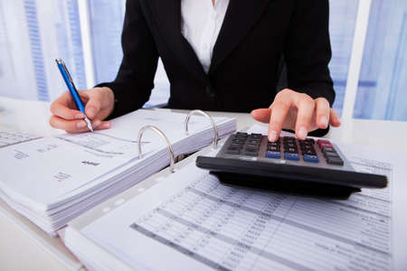 Midsection of businesswoman calculating tax at office desk 스톡 콘텐츠