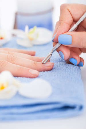 Cropped image of manicurist removing cuticle from the nail of woman at salon photo