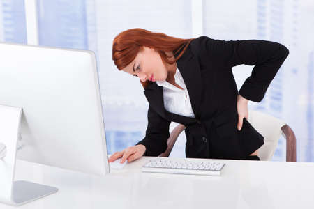 Tired young businesswoman suffering from backache while working at computer desk in office photo