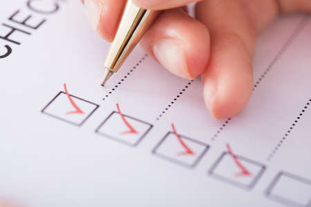 female form: Cropped image of businesswoman writing on checklist Stock Photo