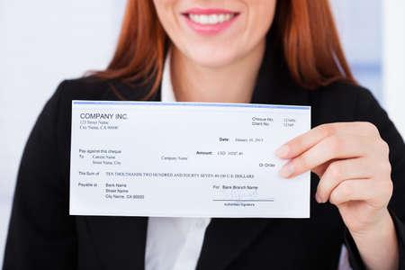 Buik van lachende zakenvrouw met check-in kantoor