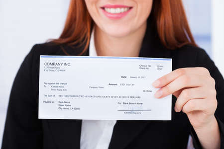 compensation: Midsection of smiling businesswoman holding cheque in office