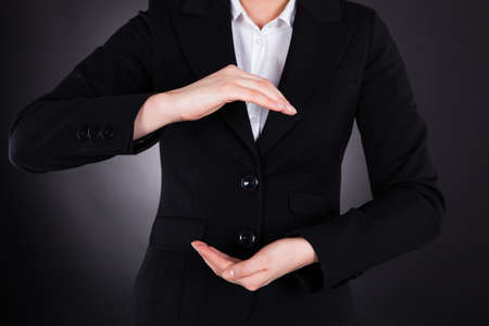 manos abiertas: Sección media de la joven empresaria con las manos abiertas aisladas sobre negro