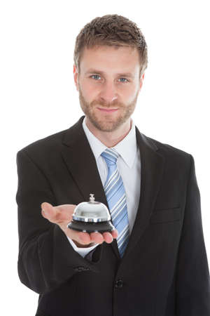 Portrait of confident businessman holding service bell over white  photo