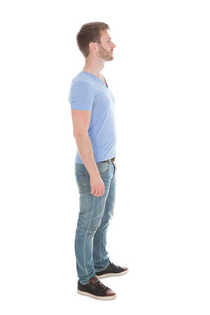 stand: Full length side view of young man standing isolated on white