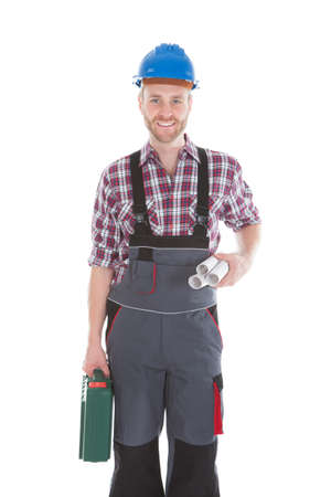 Full length portrait of confident architect holding rolled blueprints and tool kit over white  photo