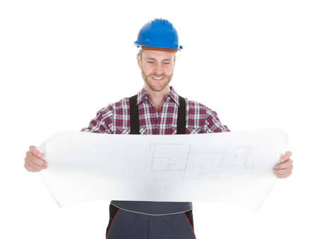Full length young male worker reading blueprint over white  photo