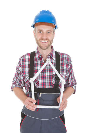 Portrait of male architect holding house frame isolated over white
