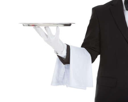 Cropped image of waiter holding empty tray over white