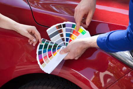 Cropped image of mechanic showing color samples to customer against car Standard-Bild