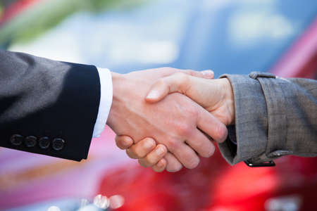 sellers: Cropped image of car dealer and female client shaking hands at dealership