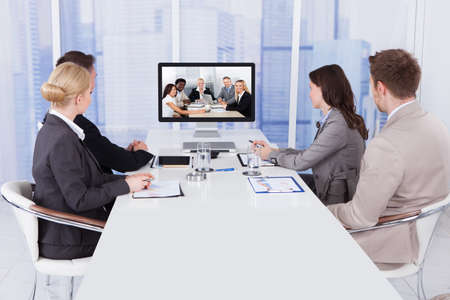 video conference: Group of business people in video conference at meeting table Stock Photo