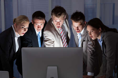 late 20s: Surprised young business people looking at computer monitor in office