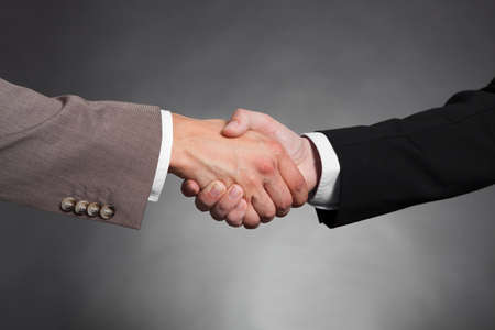 trusted: Cropped image of businessmen shaking hands against black background