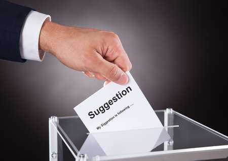Cropped image of businessman placing suggestion slip into box over black background Stok Fotoğraf