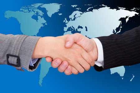 mundo manos: Recorta la imagen de los hombres de negocios dándose la mano contra el mapa del mundo. Foto de archivo