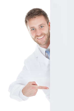 young male doctor: Portrait of happy young male doctor displaying billboard over white background Stock Photo