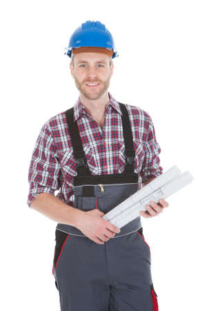 Portrait of confident architect holding rolled blueprints over white background photo