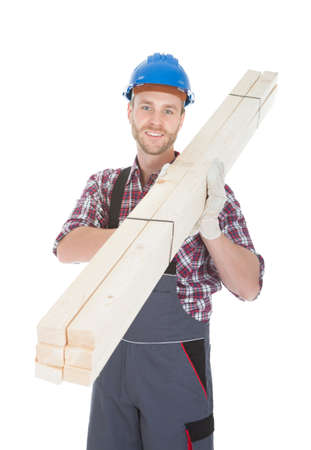 Full length portrait of young manual worker carrying wooden planks over white background photo