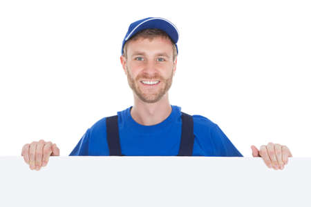 Full length portrait of smiling manual worker with billboard standing isolated over white background photo