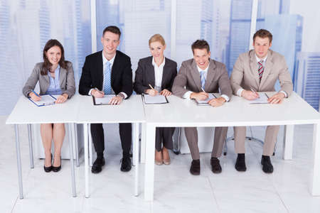 Panel of corporate personnel officers sitting at table for taking interview photo