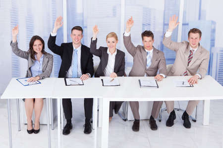 committee: Panel of corporate personnel officers sitting with hands raised at table Stock Photo