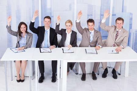 Panel de funcionarios de personal corporativo sentado con las manos levantadas en la mesa