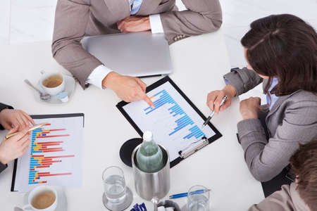 financial advisors: High angle view of young business people discussing on graph at conference table