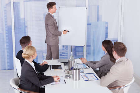 Young businessman giving presentation to colleagues at office photo