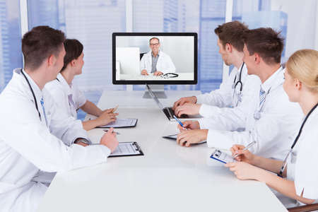 Team of doctors having video conference meeting in hospital Stock Photo