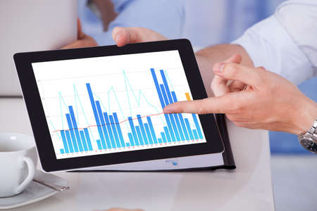 Cropped image of businessman showing graph on digital tablet to colleagues in office photo