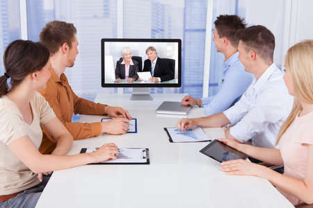 Conferences: Young business people looking at computer monitors in conference room