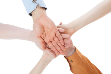 Closeup of young friends with their hands stacked together on white background photo