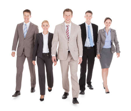 over white: Full length portrait of confident young business people walking isolated over white background Stock Photo