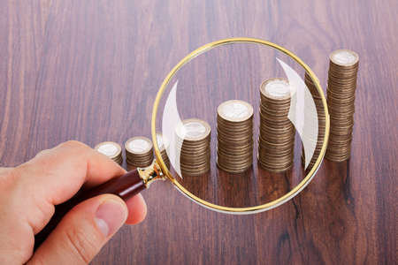 upward: Cropped image of man analyzing coin stacks with magnifying glass Stock Photo