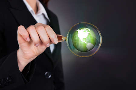 Midsection of businesswoman holding magnifying glass over globe against black background photo