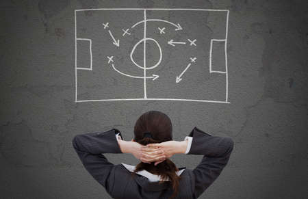 strategically: Rear view of businesswoman looking strategically game plan drawn on wall Stock Photo
