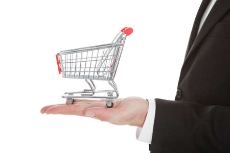 Cropped image of businessman holding shopping cart model over white background photo