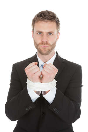 fuming: Frustrated businessman looking at tied hands over white background Stock Photo