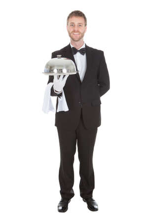 cloche: Full length portrait of confident waiter holding domed tray isolated over white background