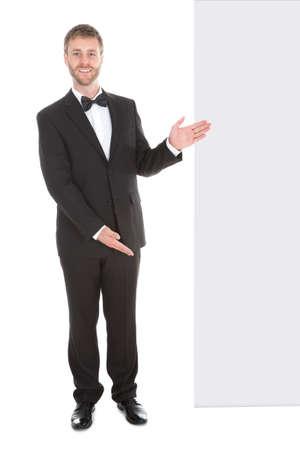 mesero: Mayordomo joven que mira la cartelera en blanco aislado m�s de fondo blanco
