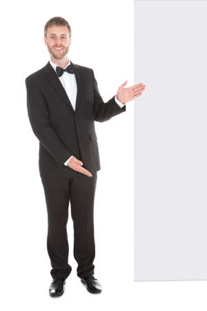 butler: Young butler looking at blank billboard isolated over white background